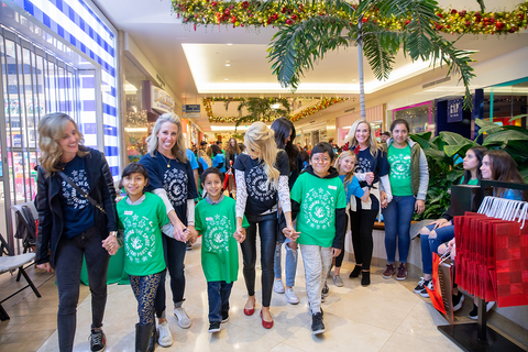 children and volunteers walking through the mall at the holiday event