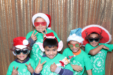 4 young children pose in a photobooth at a holiday event. They are all smiling and wearing silly costumes like big sunglasses and reindeer antlers