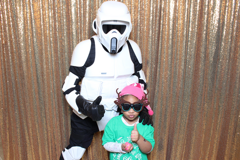 a young child wearing fun sunglasses and a hat gives a thumbs up gesture. a stormtrooper star wars character poses behind her. they are in a photobooth at a holiday event