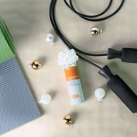HempLand USA Cannabitol Therapeutic Cream laying next to a yoga mat and jump rope, surrounded by Christmas ornaments