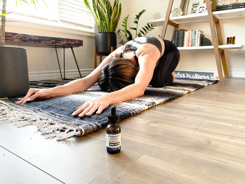 Woman doing yoga and a bottle of CBD next to her