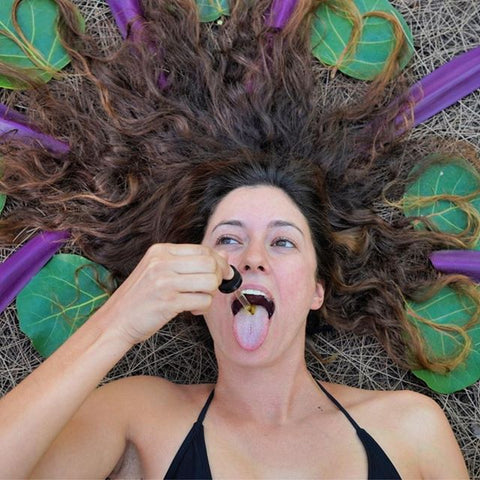 a woman lying down with her brown hair fanned out around her head. She's lying on top of a circle of green and purple leaves and shes holding a dropper of CBD above her mouth ready to drop it on her tongue