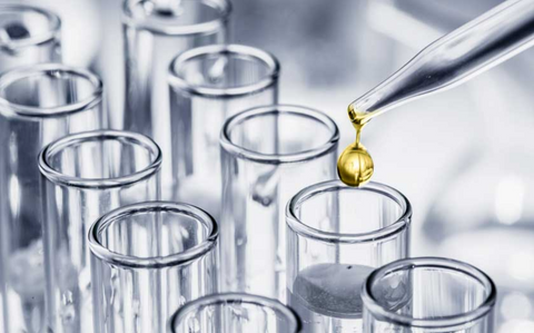 a row of lab beakers in a sterile lab with a pipette dropping amber colored liquid into a beaker