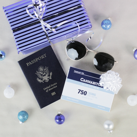 HempLand USA Cannabitol Soft Gels laying next to a US passport, aviator sunglasses, and a present surrounded by christmas ornaments