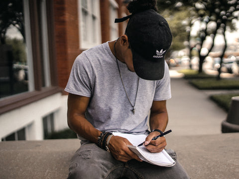 man in baseball cap sitting outside and writing in a notebook