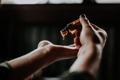A CBD bottle being dropped into a woman's open palm