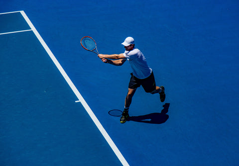 Man playing tennis on a vibrant blue tennis court