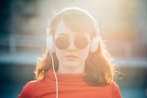 Young woman in red shirt with headphones on her ears and sunglasses with the glare of the sun on her face