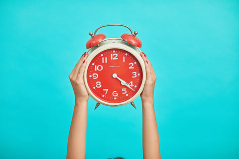 Bright blue background and red alarm clock in the foreground being held up by two hands