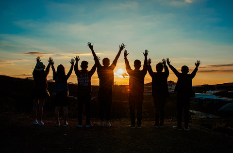 A group of individuals in a line with their hands in the air in glee. image represents teamwork