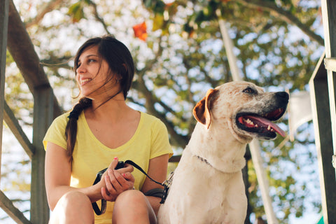 woman sitting and smiling and holding a happy dog on a leash about to go for a walk