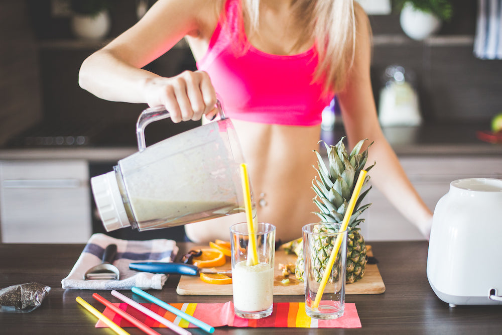 Healthy young woman making a fruit smoothie in the kitchen