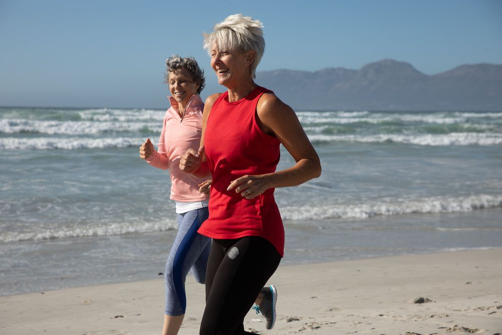 Healthy middle aged women jogging on the beach