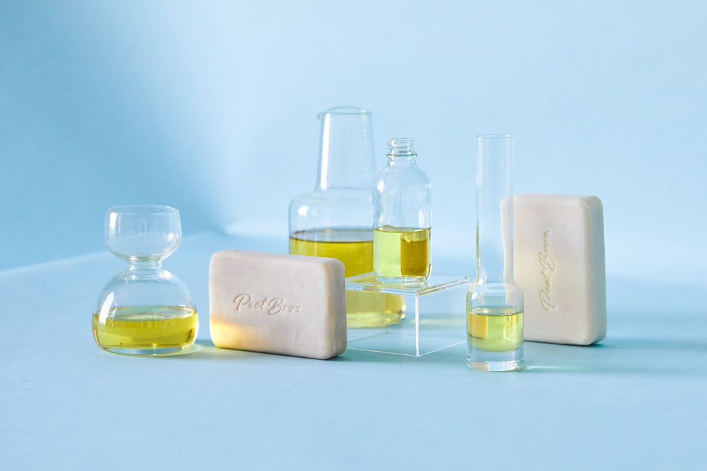 Peet Bros. Olive Oil Bar Soap surrounded by vials of golden olive oil
