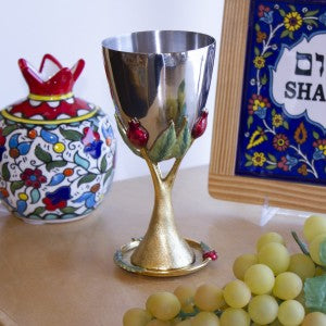 Gold kiddush cup with pomegranate design and saucer