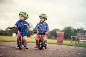 Two toddlers in a park with matching red balance bikes, green helmets and blue tops
