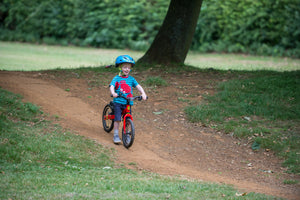 Young child on red balance bike in park