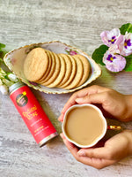 hands holding cup of tea made with radical rose blend and cookies on the side