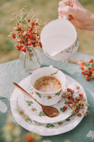 someone adding milk in cup of tea, flowers in background
