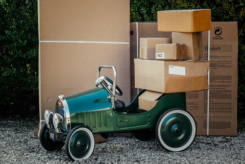 green toy vcar with packages on it and behind it