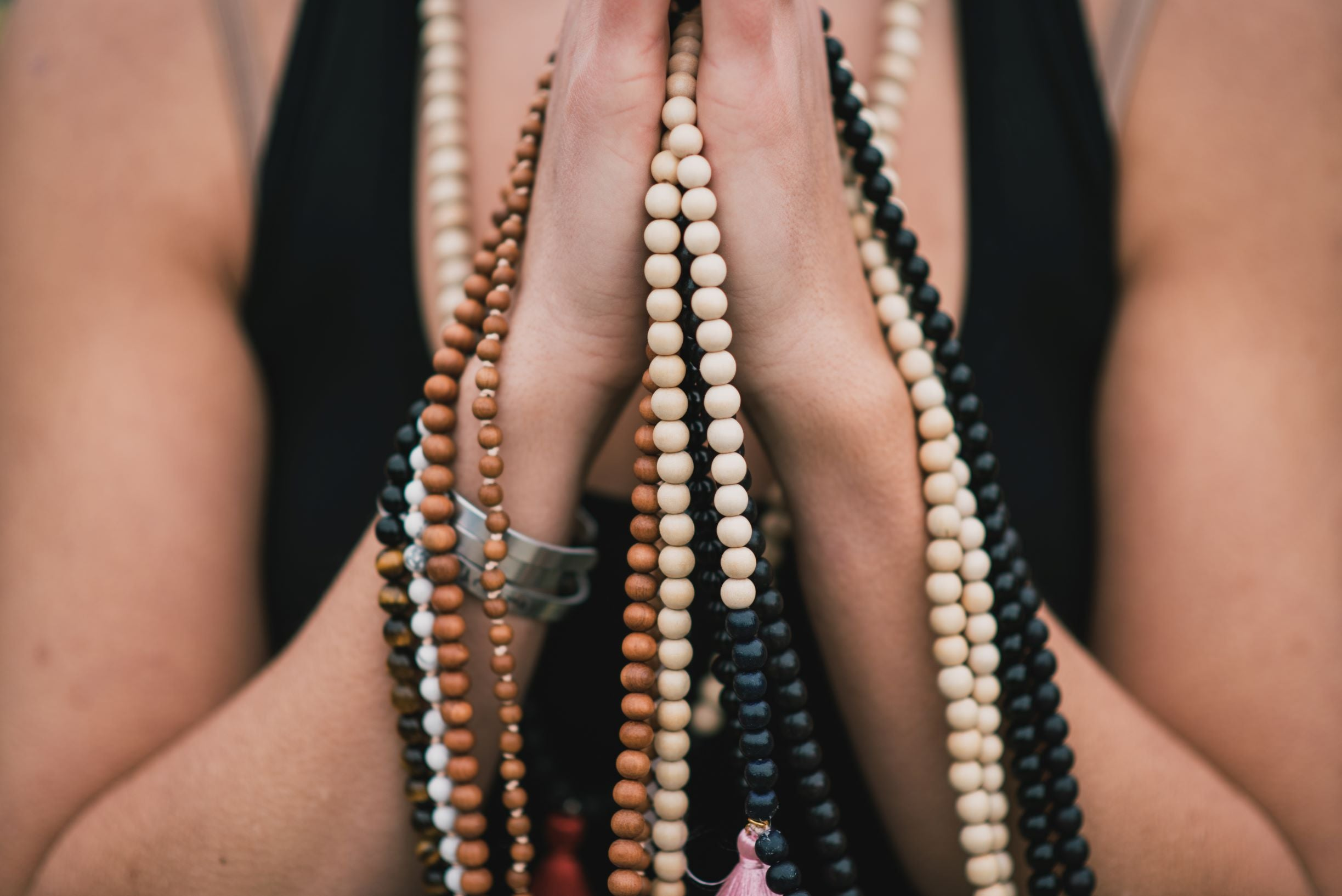 Hands held in prayer while holding handmade mala necklaces, meditating to cleanse the crystals.