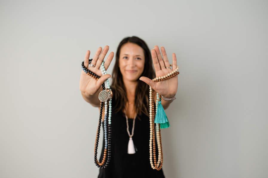 Alysia Waters from Seed + Bloom Designs holding up handmade malas which can be used to connect with affirmations.