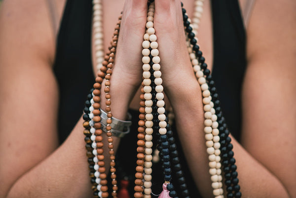 Hands held in prayer position are drapped in multiple handmade malas, made with ethically-sourced mala beads.
