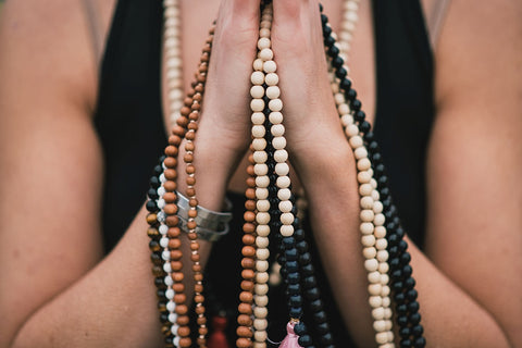 Hands in prayer position holding a collection of handmade malas using crystals for anxiety relief.