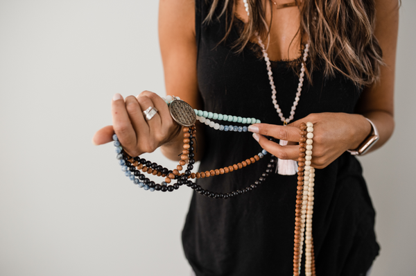 A woman holding a collection of beautiful handmade malas, often used during meditation or yoga.