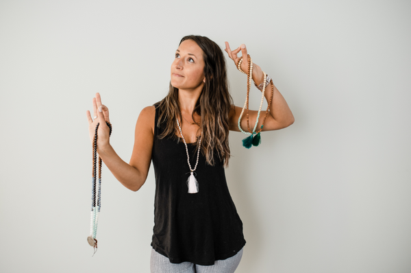 Alysia Waters of Seed + Bloom Designs holds a yoga pose while practicing mindfulness with handmade malas.