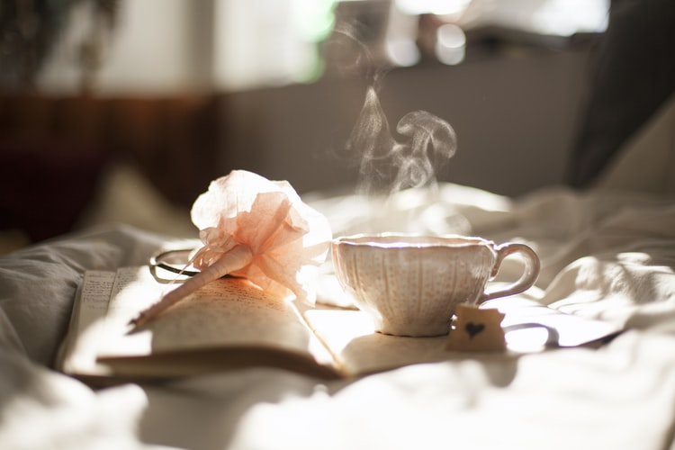 A journal sitting on a bed  with tea and a pen with positive affirmations written inside.