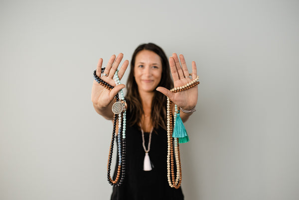 Alysia Waters of Seed + Bloom Designs holding up her hands holding beautiful handmade malas.