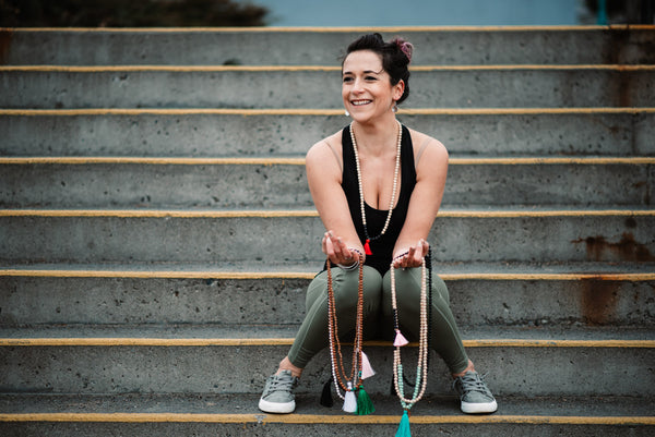 Alysia Waters of Seed + Bloom Designs sits on an outdoor staircase while holding a collection of homemade malas.