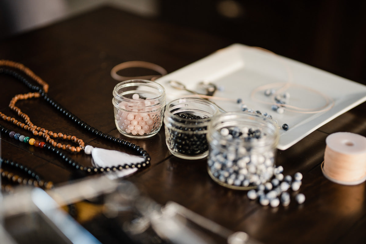 A collection of ethically-sourced mala beads and other jewelry-making tools sits on a table.