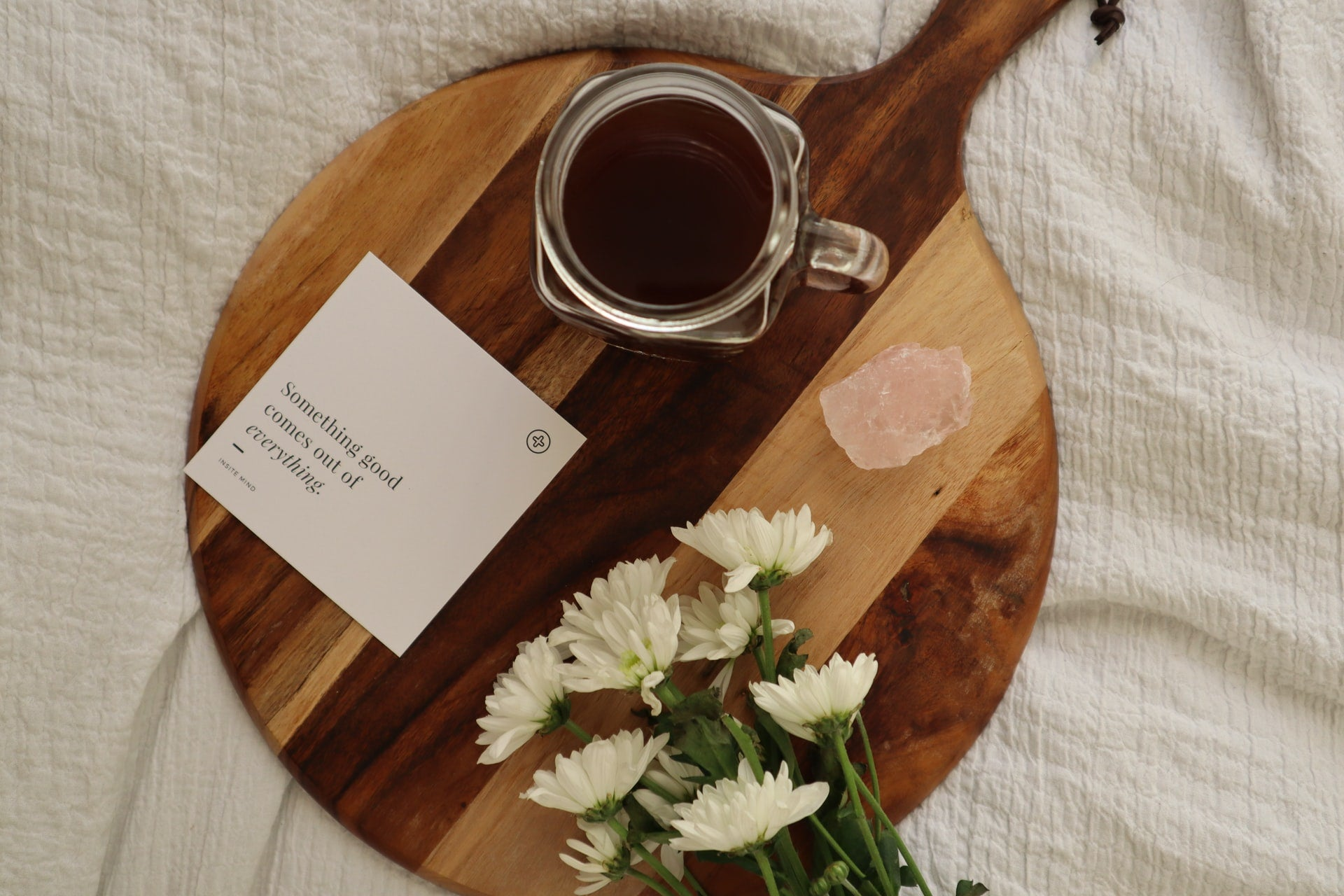A positive affirmation card sitting beside a cup of tea and flowers.