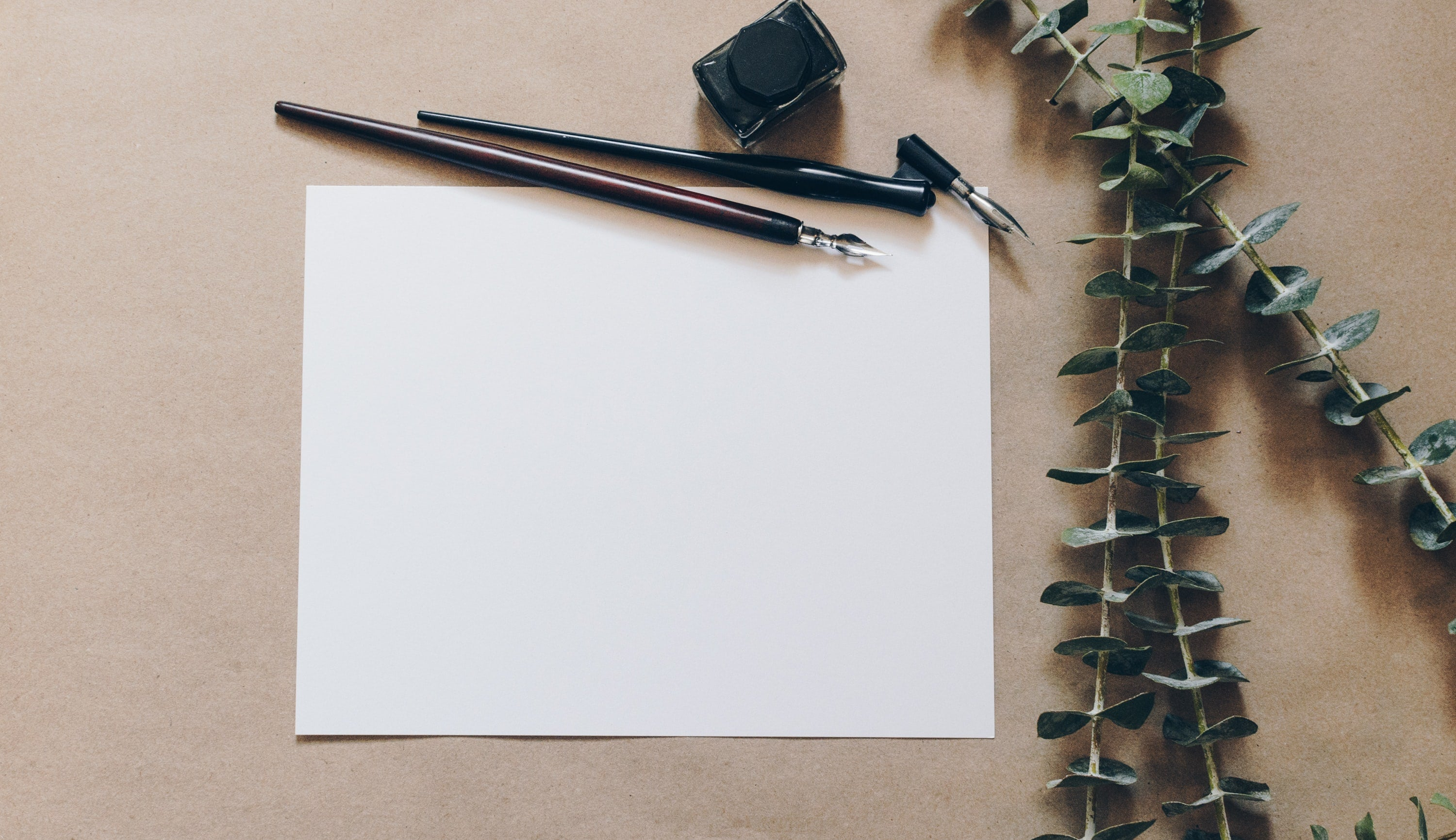 A blank piece of paper with calligraphy pens and flowers, ready to write a nice letter for someone.