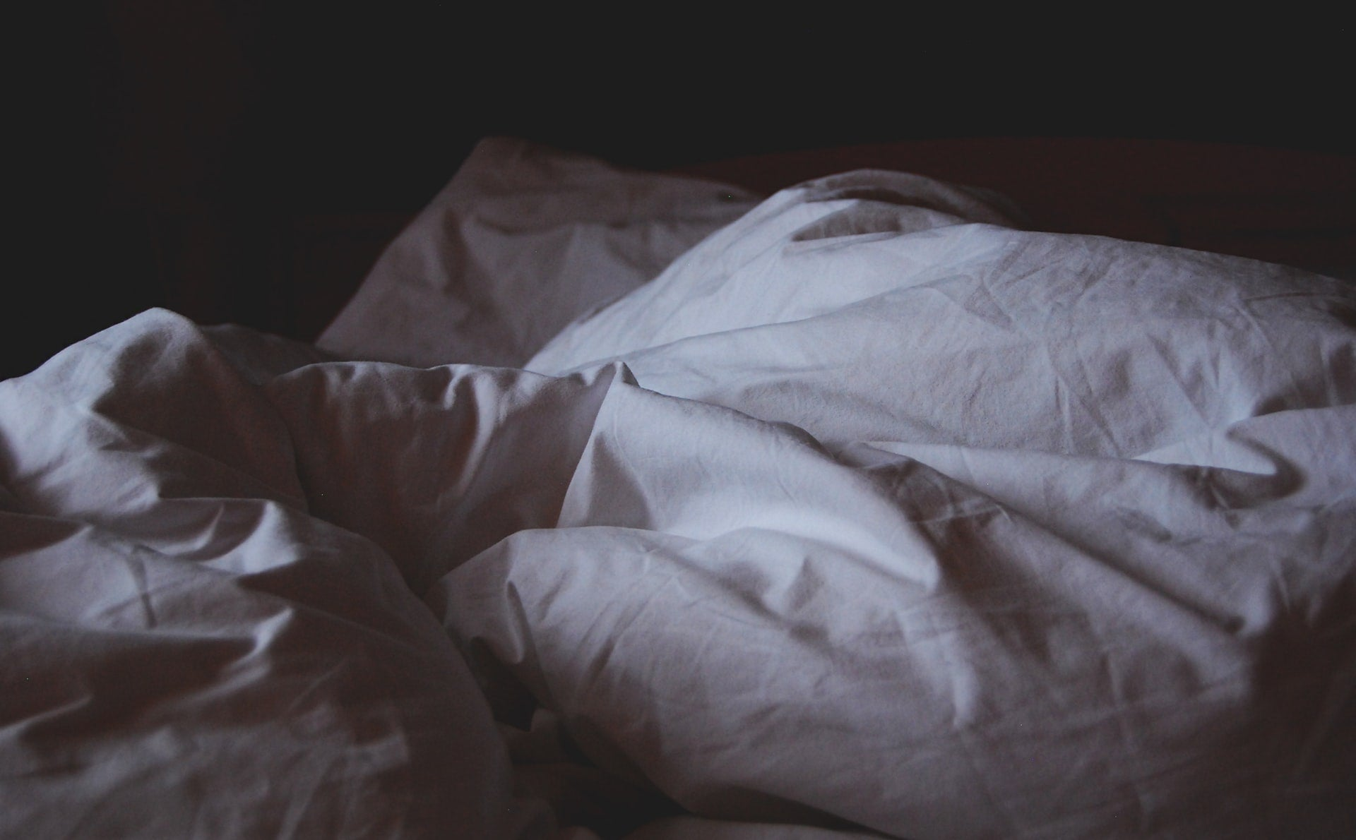 A comfortable bed with a weighted blanket for anxiety.