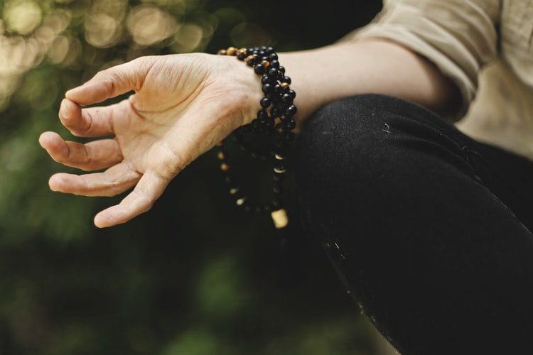 A hand in a meditation position, with the thumb and pointer finger touching, while wearing a black mala bracelet.