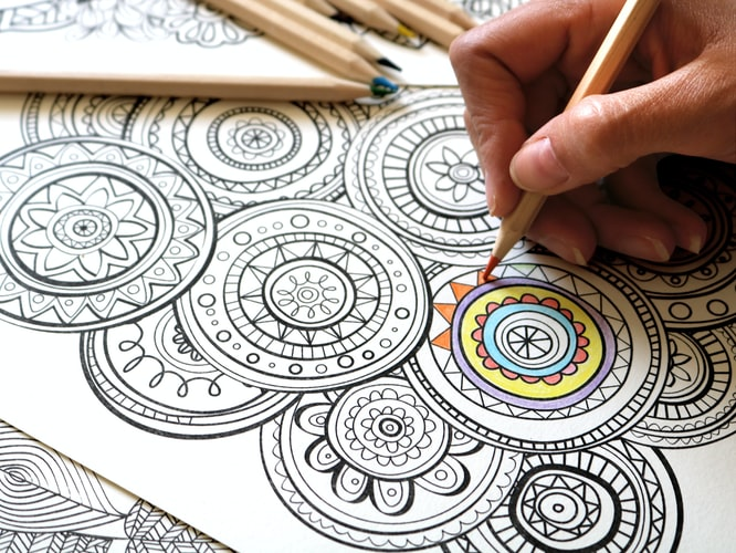 A mindful colouring page being filled in by a hand holding an orange pencil.