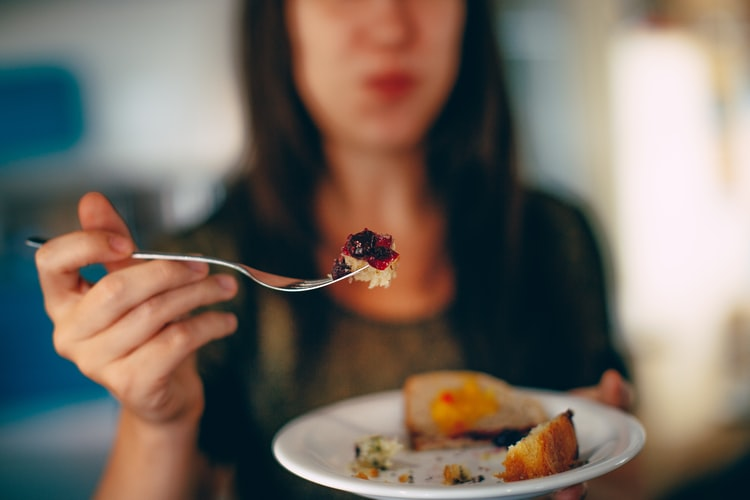 A woman holds up a bite of cake on a fork.