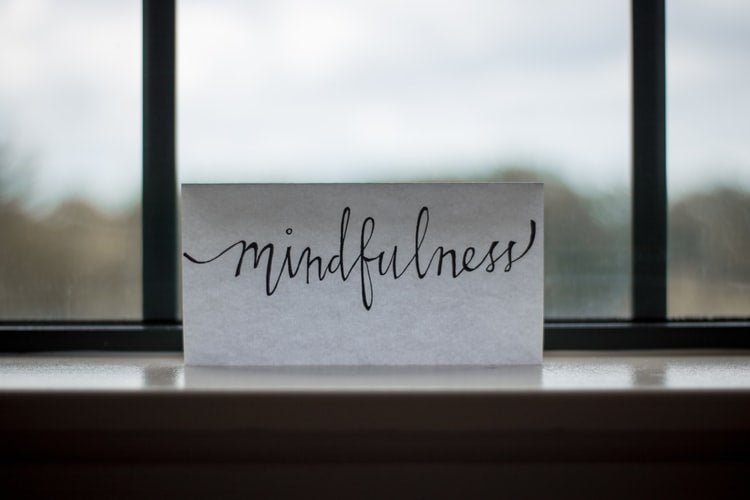 The word 'mindfulness' written on a piece of paper sitting on a ledge in front of a window.