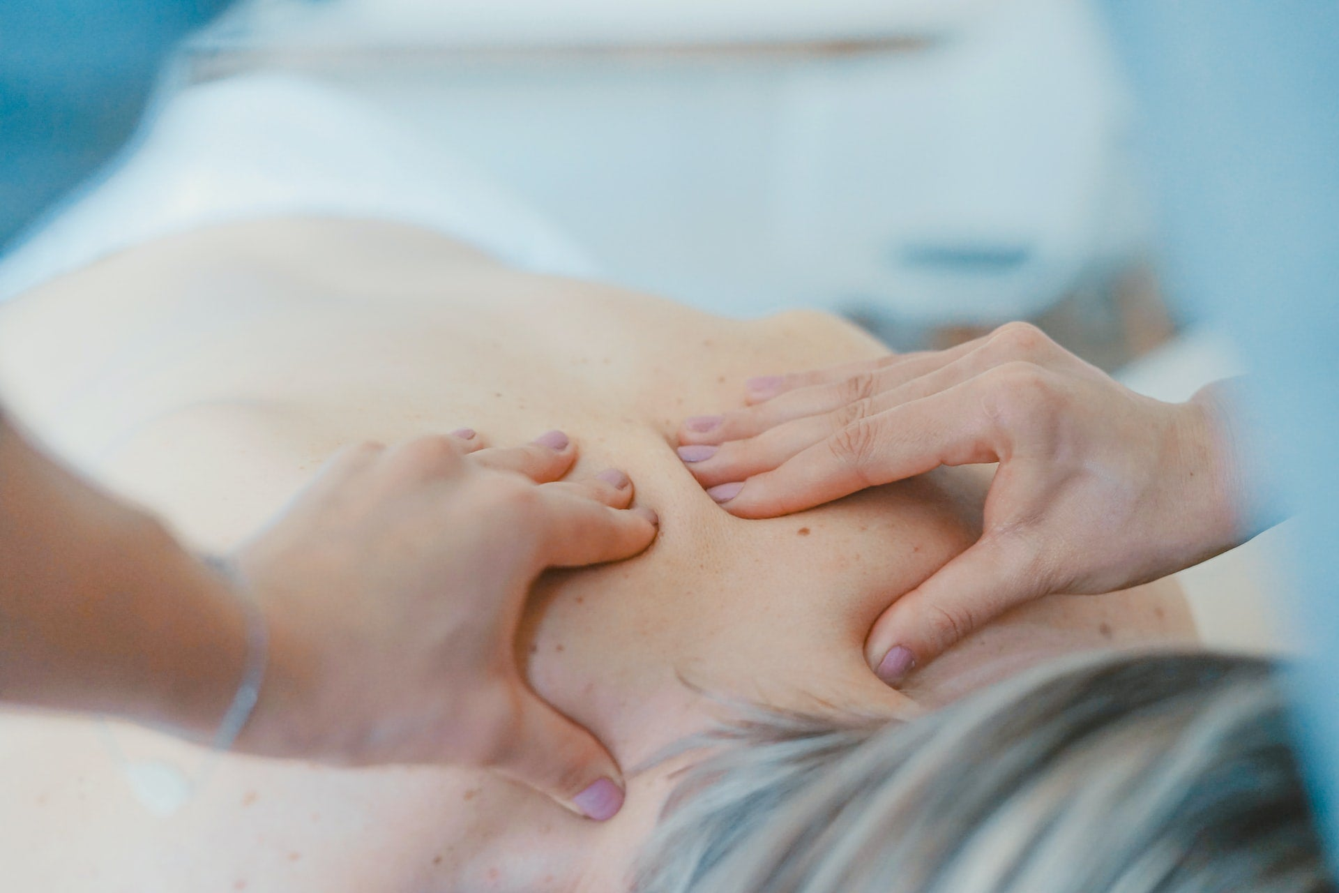 A person laying face-down receiving a back massage to ease anxiety and stress.