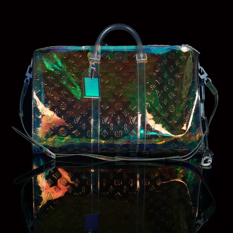 Louis Vuitton-Keepall-L 50 x H 22 x W 29 cm/L 19.7 x H 8.7 x W 11.4 inches Iridescent Prism Transparent embossed Monogram PVC PVC trim White detailing Top handle for hand or elbow carry Leather handle fastener Double zip closure Leather-covered padlock ornament Resin chain Removable leather strap for shoulder or cross-body carry-fabriqe.com