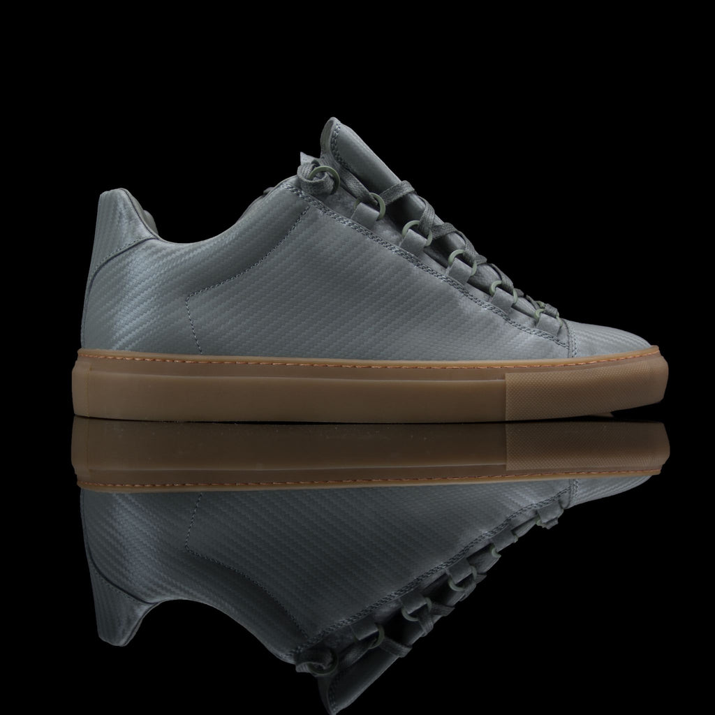 Balenciaga-Arena-Product Code: Colour: Khaki Carbon Fibre - Gum Sole Discontinued Material: Leather, Rubber Sole BALENCIAGA, the Paris based label drops the Arena Low. The casual sneakers are composed in Khaki Carbon Fibre Leather and Gum Sole. Also, the quilted section at back, tone on tone laces and the round toe gives them a rugged look.-fabriqe.com