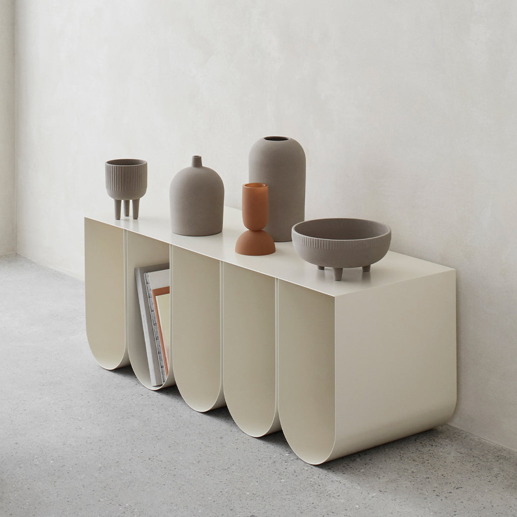 Terracotta medium bowl on white curved bench, all designed by Kristina Dam