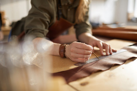 A skilled artisan woman handcrafts a leather bag for JANE & CLAY CO.