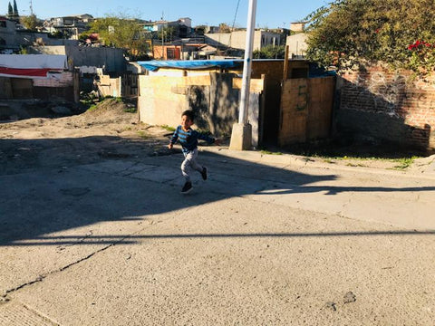 A young boy runs through the streets of Tijuana, Mexico, which is ripe with poverty