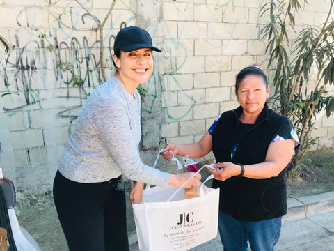 Janeth Moyal, CEO of JANE & CLAY CO., presents a bag full of food and other necessities to a giving tour recipient