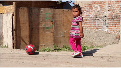 A young girl plays soccer in an impoverished town in the Baja California, Mexico area