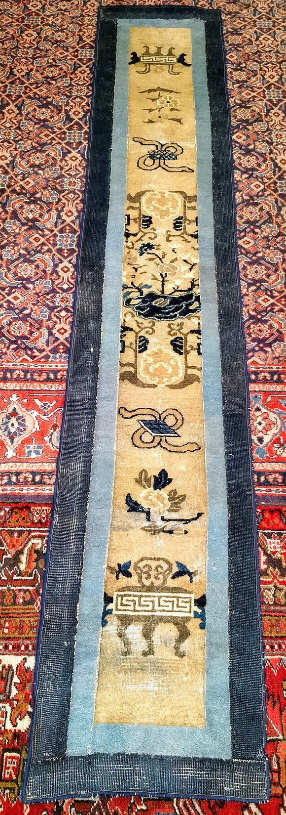 Beautiful Chinese Peking runner from the late 1800s. A number of traditional Chinese designs are set in a column in the cream/straw color field.  The borders in this Chinese Peking rug are dark and light colors that frame beautifully the design in this antique runner.